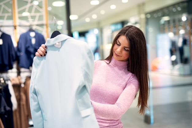 Młoda, piękna, skupiona dziewczyna bada kobiece bluzki, stojąc w sklepie.