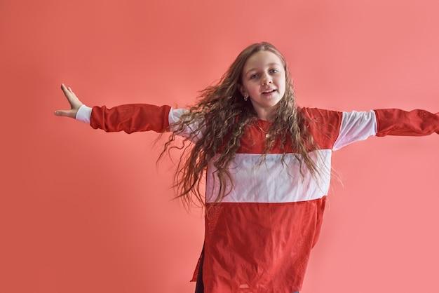 Młoda piękna śliczna dziewczyna tańczy, nowoczesna szczupła nastolatka w stylu hip-hop skacze