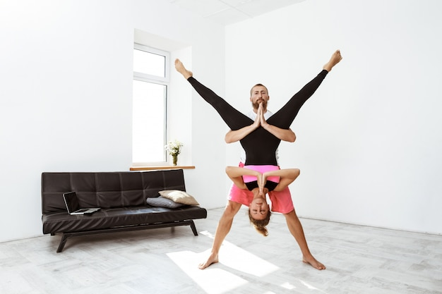 Młoda piękna sportive para ćwiczy partnera joga asany w domu.