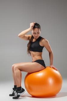 Młoda, piękna, sportowa dziewczyna robi ćwiczenia na fitball
