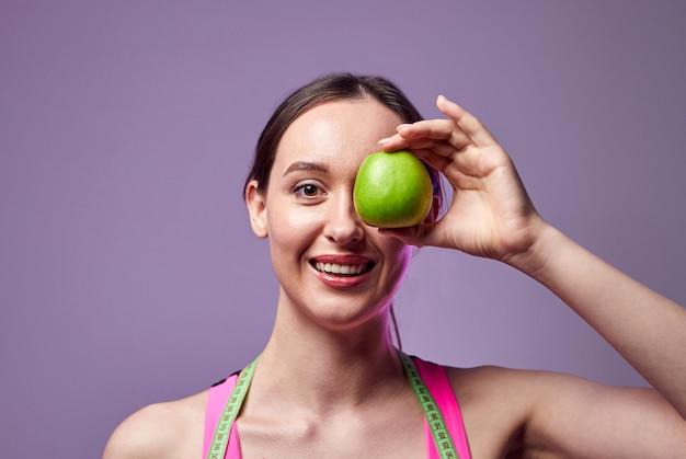 Młoda piękna sportowa dziewczyna w legginsach i topie z centymetrem na szyi trzyma zielone jabłko. zdrowy tryb życia.