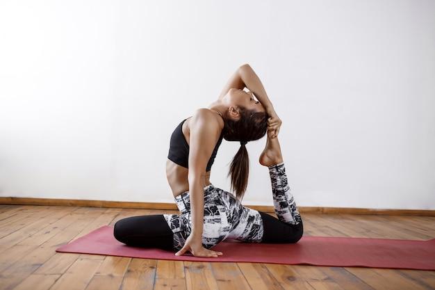 Młoda piękna sportowa kobieta ćwiczy salowy joga na czerwieni macie