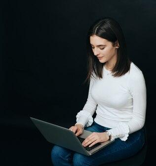 Młoda piękna studencka kobieta pracuje na laptopie nad ciemnym tłem