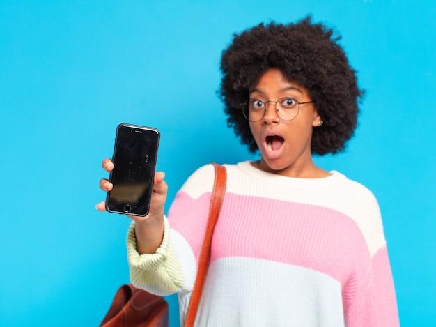 Młoda piękna studentka afro kobieta z inteligentny telefon