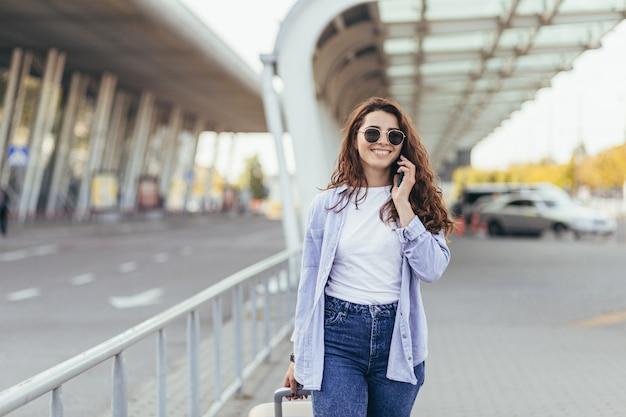 Młoda piękna studentka opuszcza lotnisko w nowym mieście i czeka na taksówkę