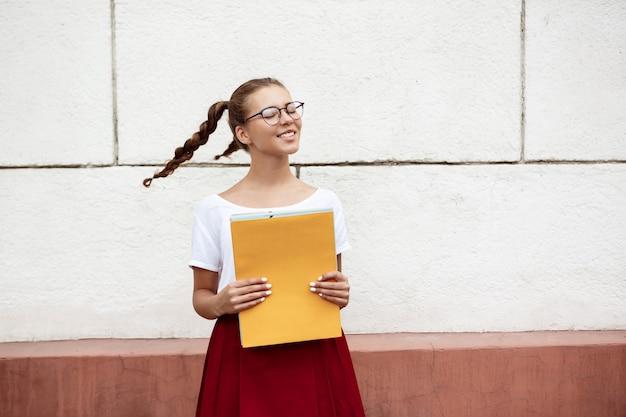 Młoda piękna studentka w okularach, uśmiechając się, trzymając foldery na zewnątrz