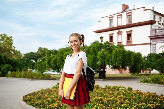 Młoda piękna studentka w okularach uśmiechnięta, trzymając foldery na zewnątrz, powierzchnia parku