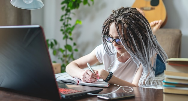 Młoda piękna studentka z dredami uczy się na lekcji online w domu w pokoju z laptopem