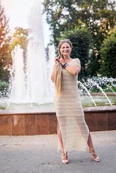 Młoda piękna stylowa dziewczyna pozuje w mieście, w pobliżu fontanny