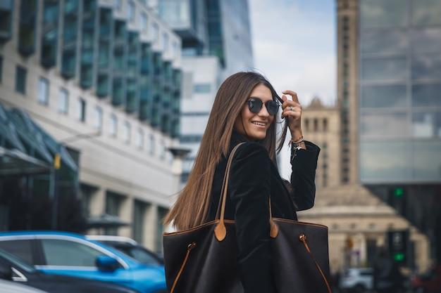 Młoda piękna stylowa dziewczyna w okularach przeciwsłonecznych chodzi na ulicie. portret kobiety z bliska odwraca się do kamery i uśmiecha się.