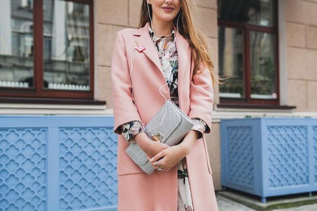 Młoda piękna stylowa kobieta spaceru na ulicy w różowym płaszczu, trzymając torebkę w rękach, słuchając muzyki