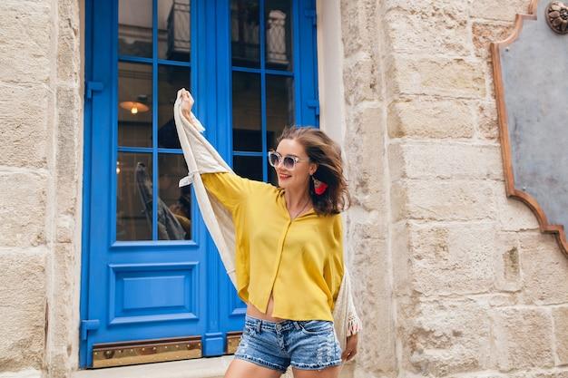 Młoda piękna stylowa kobieta spaceru w starej ulicy miasta