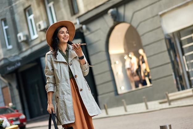 Młoda piękna stylowa kobieta ubrana w jesienny płaszcz i kapelusz, rozmawiając na smartfonie i uśmiechając się podczas