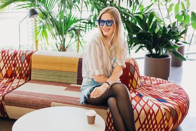 Młoda piękna stylowa uśmiechnięta kobieta siedzi w kawiarni hipster na kanapie na sobie koszulę i niebieskie okulary przeciwsłoneczne