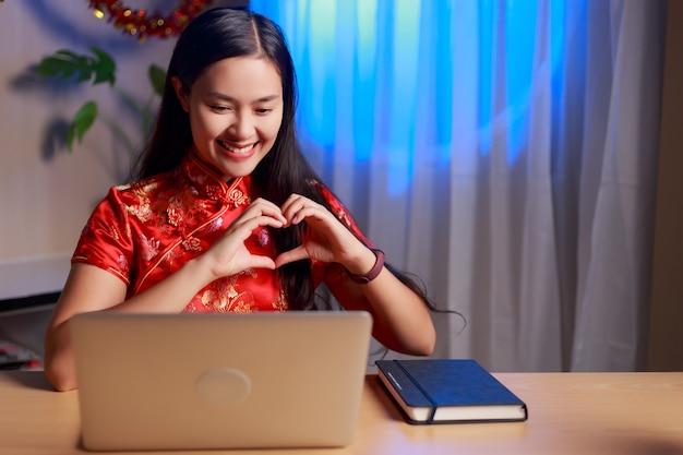 Młoda piękna szczęśliwa azjatycka kobieta ubrana w strój chińskiej tradycji podejmowania wideokonferencji, czyniąc ręce w kształcie serca, opowiadając miłość i świętując chiński nowy rok w domu.