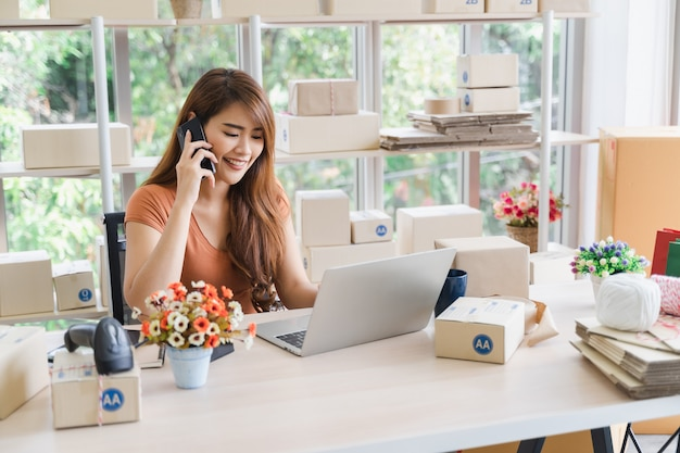 Młoda piękna szczęśliwa azjatykcia biznesowa kobieta w przypadkowej odzieży z uśmiechniętą twarzą dzwoni dla otrzymywa rozkazy klient z laptopem przy jej początkowym domowym biurem, sme pojęcie