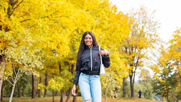 Młoda piękna, szczęśliwa czarna dziewczyna w modnych, casualowych ubraniach wygląda z modną torebką spacery w parku z jasnymi złotymi jesiennymi liśćmi
