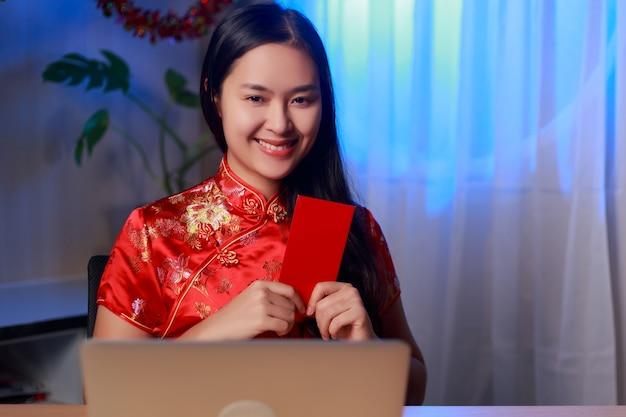 Młoda piękna szczęśliwa kobieta azji na sobie sukienkę chińskiej tradycji siedzi przed laptopem trzymając czerwoną kopertę z buźką świętuje chiński nowy rok w domu.