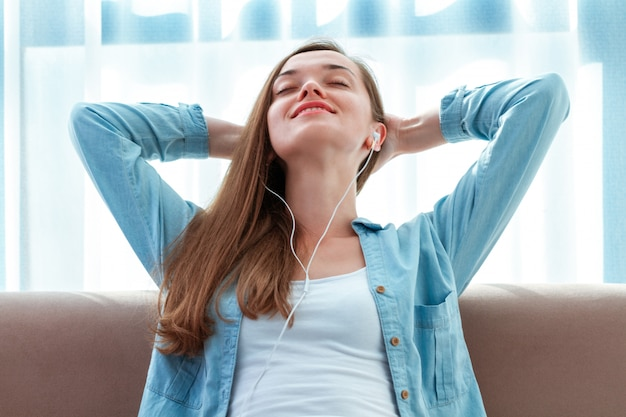 Młoda, piękna, szczęśliwa kobieta odpoczywająca w słuchawkach słuchająca relaksującej muzyki na kanapie w domu po długim dniu pracy i ciesząca się samotnością, spokojem