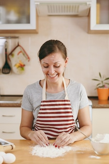 Młoda piękna szczęśliwa kobieta siedzi przy stole z mąką i przygotowuje ciastka w kuchni. gotowanie w domu. przygotuj jedzenie.