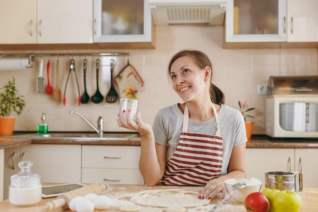 Młoda piękna szczęśliwa kobieta siedzi przy stole z mąką i wycina szklankę w cieście kręgi na pierogi w kuchni. gotowanie w domu. przygotuj jedzenie.