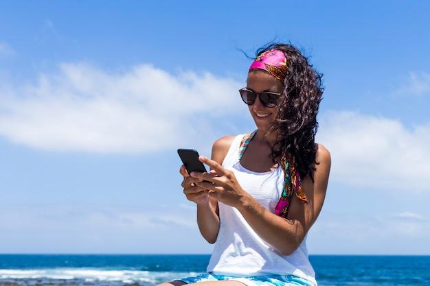 Młoda piękna szczęśliwa kobieta używa telefon komórkowego nad jasnym błękitnym tłem. lato. styl życia