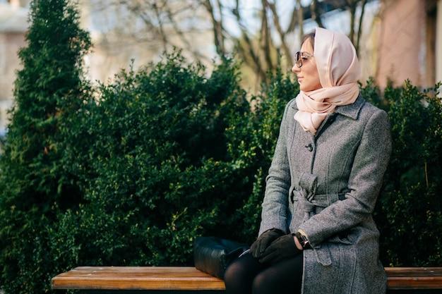 Młoda piękna szczęśliwa kobieta w płaszczu siedzi na ławce w parku