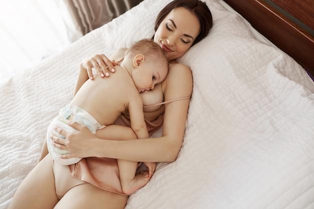 Młoda piękna szczęśliwa mama karmi piersią przytulanie swojego synka leżącego na łóżku w domu