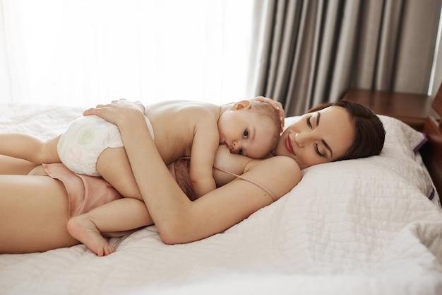 Młoda piękna szczęśliwa mama karmiąca piersią przytulanie dziecka leżąc na łóżku w domu.