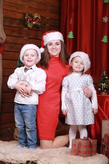 Młoda piękna szczęśliwa mama z małym synem i córką w czapkach mikołaja świętuje boże narodzenie i nowy rok w domu. rodzina, szczęście, święta, koncepcja bożego narodzenia.