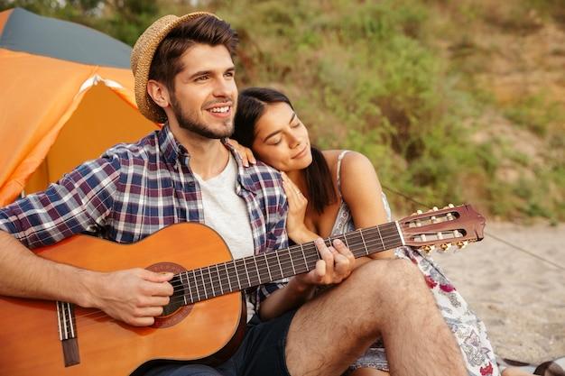 Młoda piękna szczęśliwa para gra na gitarze siedząc na plaży