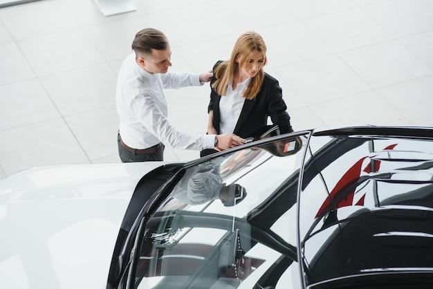 Młoda piękna szczęśliwa para kupuje samochód. mąż kupuje samochód dla żony w salonie. koncepcja zakupów samochodów.