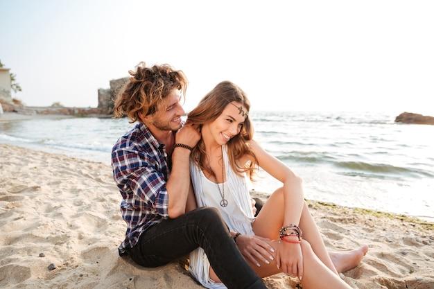 Młoda piękna szczęśliwa para zakochanych flirtuje siedząc na plaży