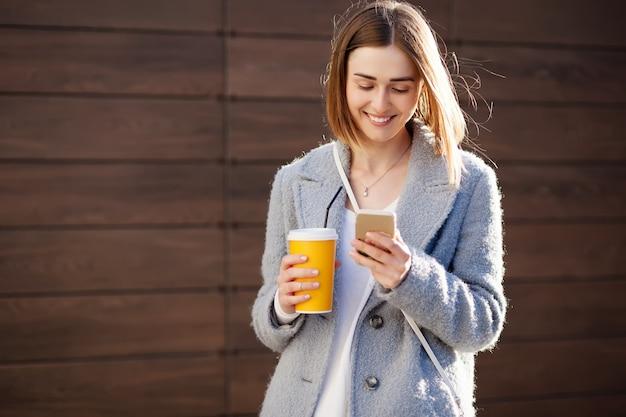 Młoda piękna szczęśliwa stylowa modniś dziewczyna z koktajlem, smoozy napojem