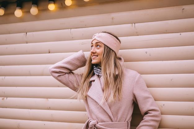 Młoda piękna szczęśliwa uśmiechnięta dama w stylowym zimowym lekkim bandażowym szaliku w różowym płaszczu pozuje