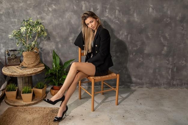 Młoda piękna szczupła biznesowa kobieta siedzi na wiklinowym krześle