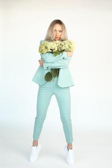Młoda piękna szczupła blondynka z długimi włosami w miętowozielonych spodniach i tenisówkach z naręczem kwiatów hortensji w dłoniach, na pełnej wysokości na białym tle..