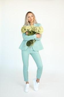 Młoda piękna szczupła blondynka z długimi włosami w miętowym zielonym spodniach i trampkach z naręczem kwiatów hortensji w dłoniach na pełnej wysokości na białym tle. . zdjęcie wysokiej jakości