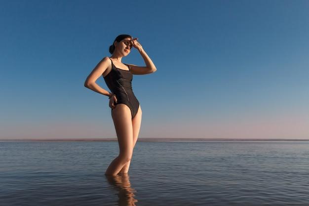 Młoda piękna, szczupła kobieta w czarnym stroju kąpielowym stoi na morzu i ogląda zachód słońca