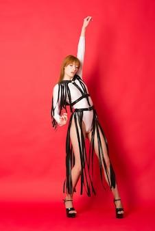 Młoda piękna tancerka pozowanie w studio na czerwonym tle