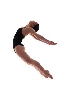 Młoda piękna tancerka pozuje na tle studia