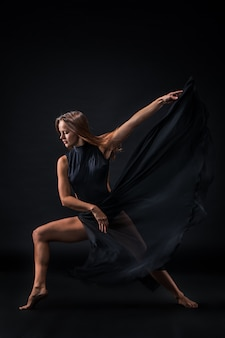 Młoda piękna tancerka w beżowej sukience tańczy na czarnej ścianie
