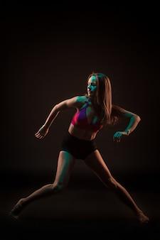 Młoda piękna tancerka w beżowej sukience tańczy na czarno