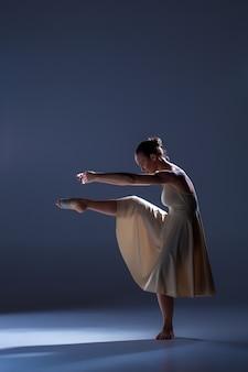 Młoda piękna tancerka w beżowej sukience tańczy na szarym tle studia