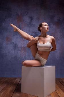 Młoda piękna tancerka w beżowym stroju kąpielowym pozuje na białym sześcianie na liliowym studio