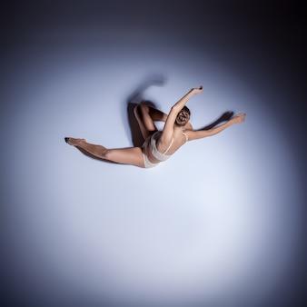 Młoda piękna tancerka w beżowym stroju kąpielowym tańczy na liliowym tle podłogi