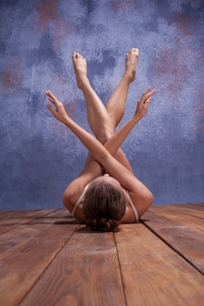 Młoda piękna tancerka w beżowym stroju kąpielowym tańczy na tle liliowego studia na drewnianej podłodze
