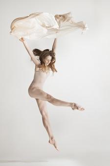 Młoda piękna tancerka w beżowym stroju kąpielowym, taniec na szaro