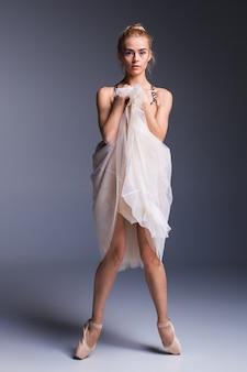 Młoda piękna tancerka w nowoczesnym stylu pozuje na tle studia