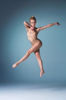 Młoda piękna tancerka w nowoczesnym stylu skacząca na niebiesko studio